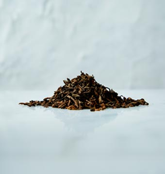 A heap of dark brown Pu-Erh tea Leaves on a marbled surface