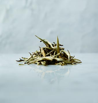 Large white tea leaves on a marbled surface
